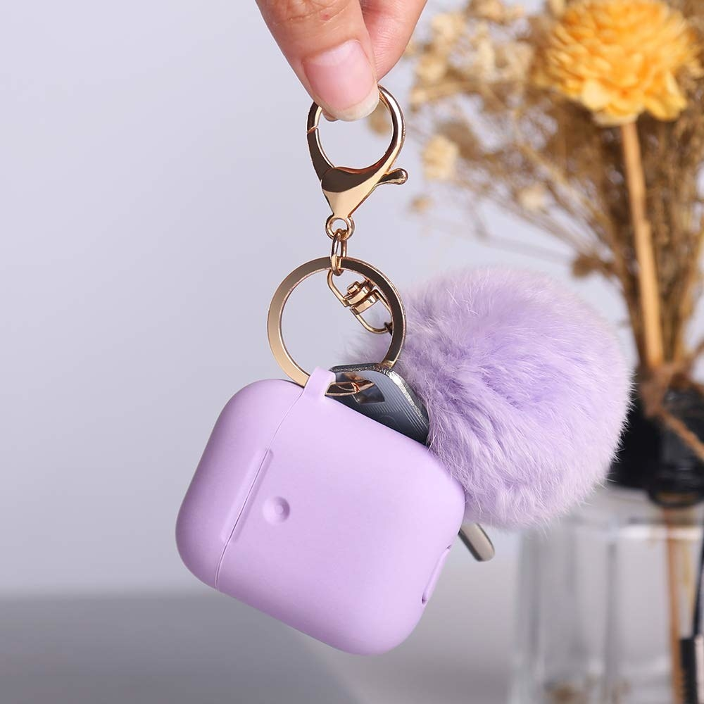 lavender Airpods case with a lavender pom pom on a keychain and a car ckey