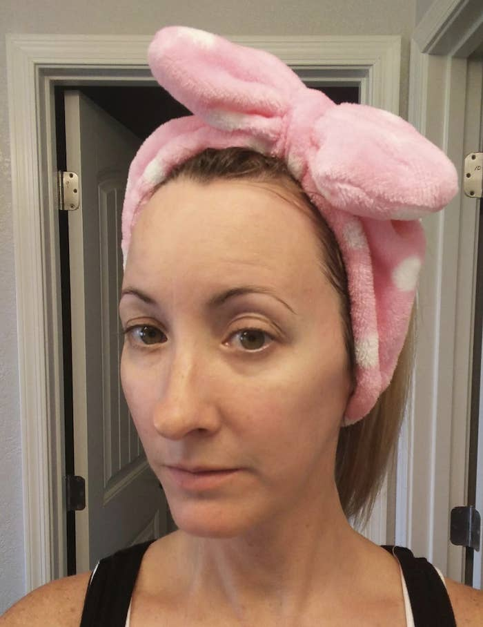 A woman wearing a pink cloth headband that has a big bow at the top for style.
