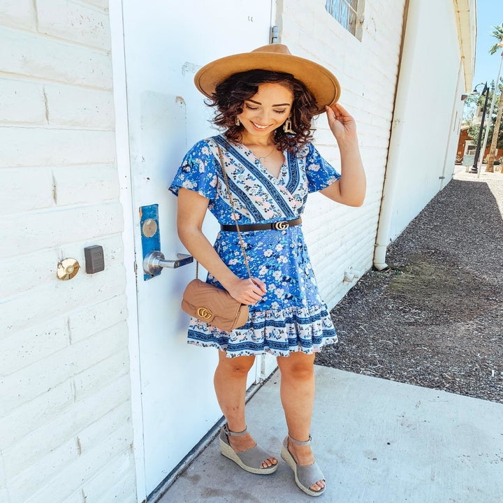 reviewer wearing the v-neck dress in a blue print pattern