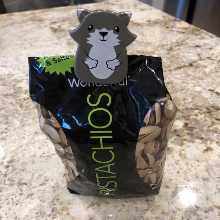reviewer's bag of pistachios with a gray and white animated fox clip to keep it closed