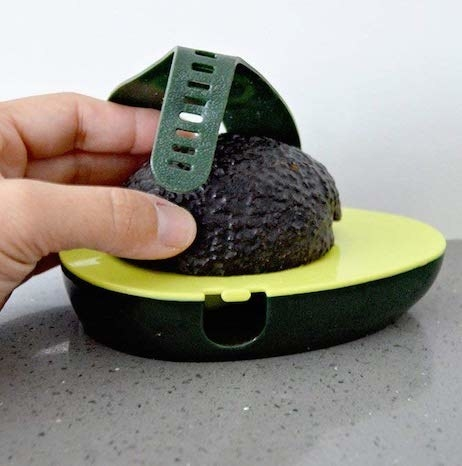 a half-avocado sitting inside the avocado saver with a strap across it to keep it face down so it doesn't get all brown and nasty