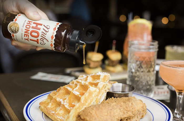 a model's hand pouring mike's hot honey on chicken and waffles