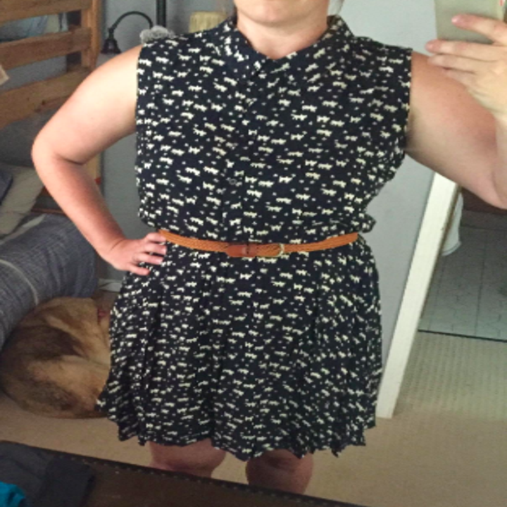 A reviewer wearing the dress in black and white cat print. it hits above the knee