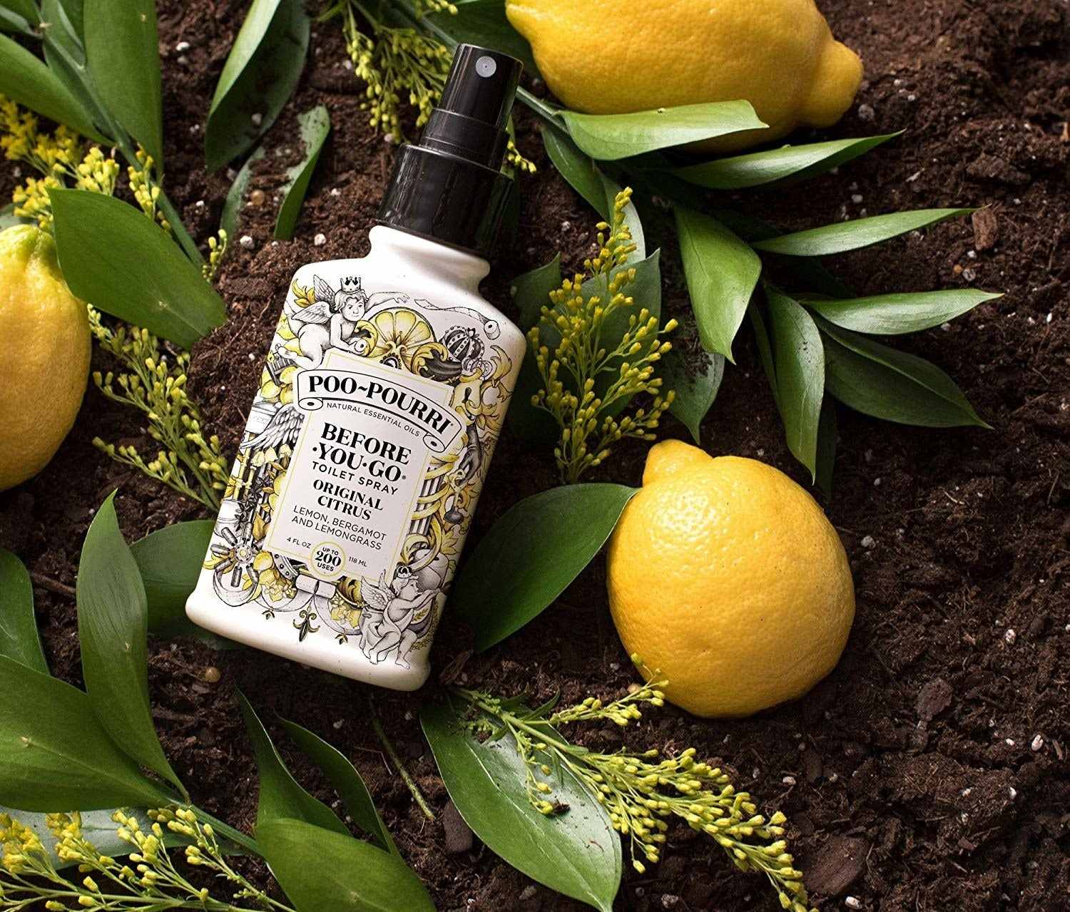 A bottle of lemon-scented toilet spray placed artfully on soil with lemons and leaves around it