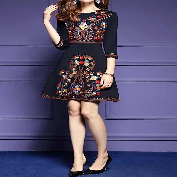 A model wearing the black three-quarter sleeve dress with red, yellow, and blue floral embroidery