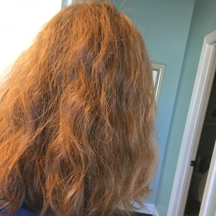 A reviewer's wavy, frizzy hair before using the hot air brush