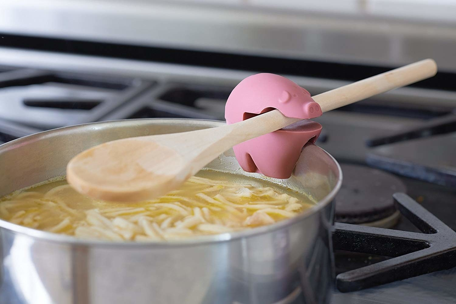 A pig-shaped utensil holder clamped over a pot full of soup and pasta A wooden spoon is sitting the pig's mouth