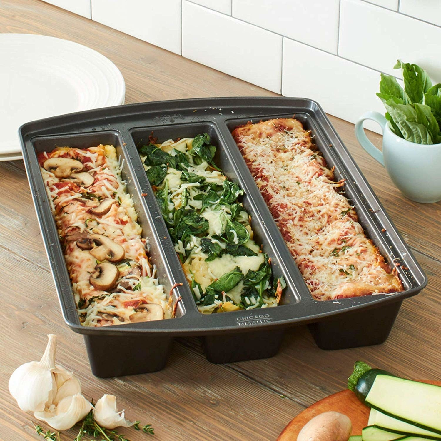 A stainless steel baking pan with three sections that have lasagna in them