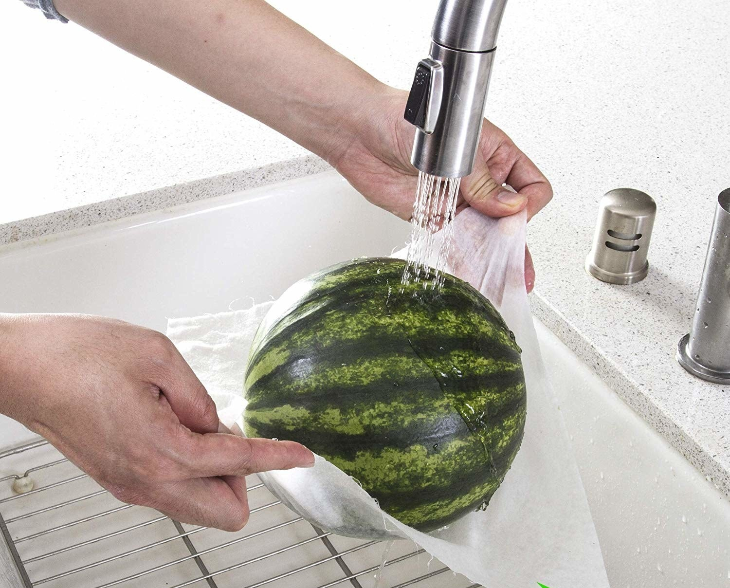model holds a whole watermelon up under sink with paper towel