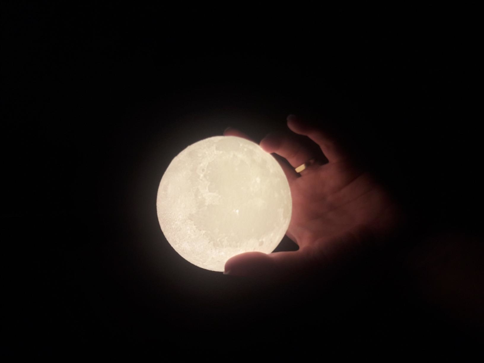 hand holds glowing moon light