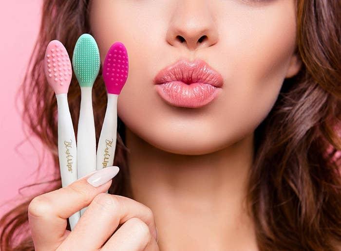 a model holding three lip scrubbing brushes
