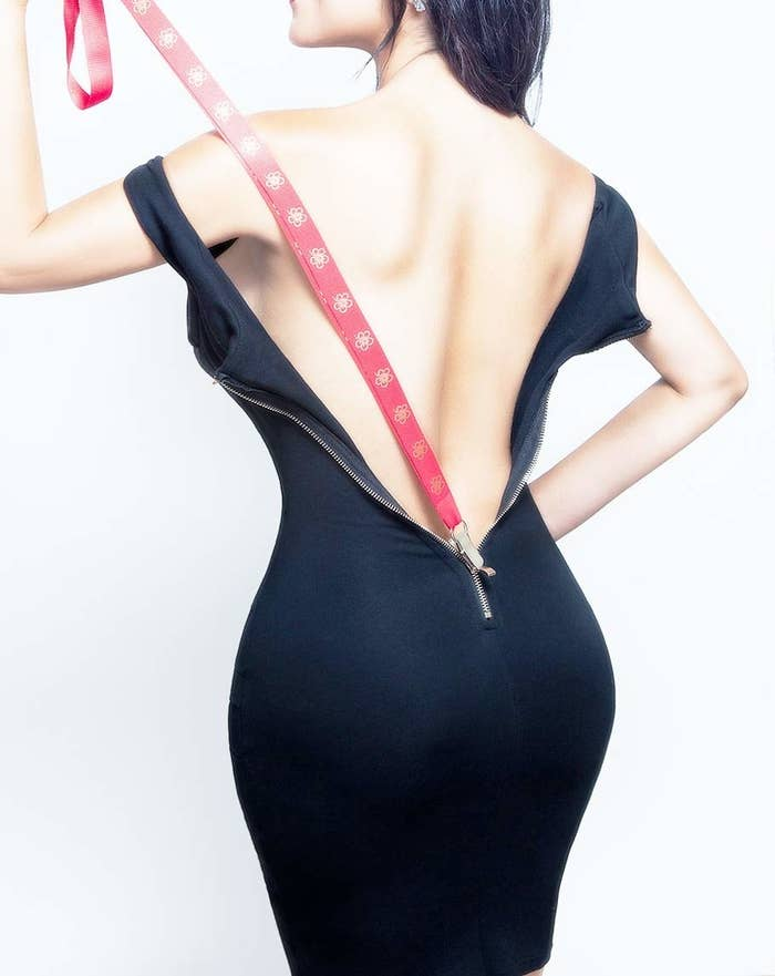 model closes back of dress with long clippy strap