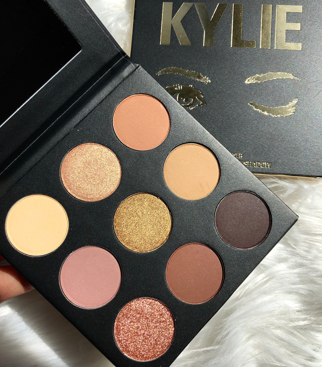 a palette with an array of yellow, pink, and shimmery eyeshadow colors
