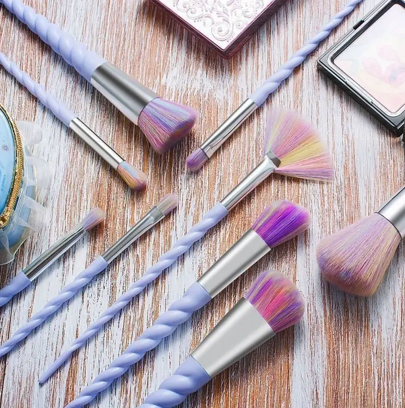 a makeup brush set with twisted purple handles that look like unicorn horns and rainbow bristles