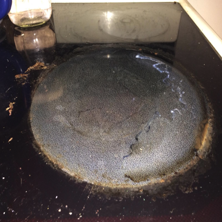 reviewer's black stovetop eye with burnt marks all over it and other grime