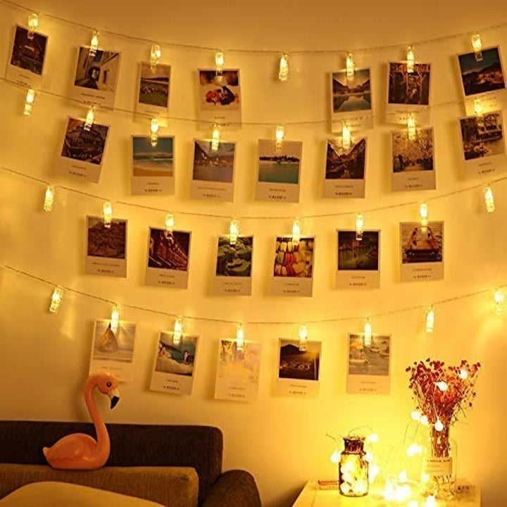 the photo lights strung up against the wall, holding photos