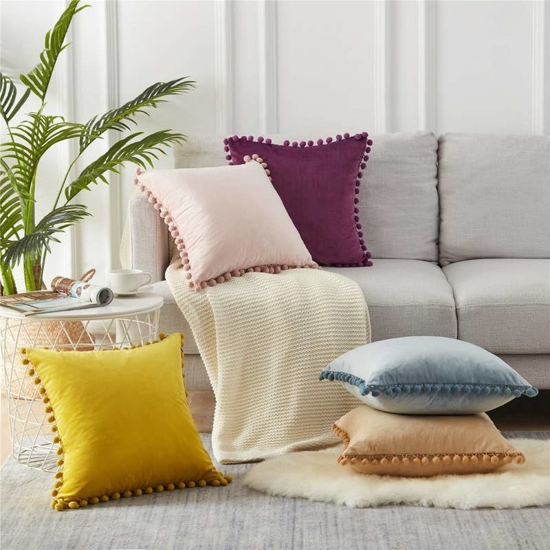 the square velvet pillows on a couch and floor