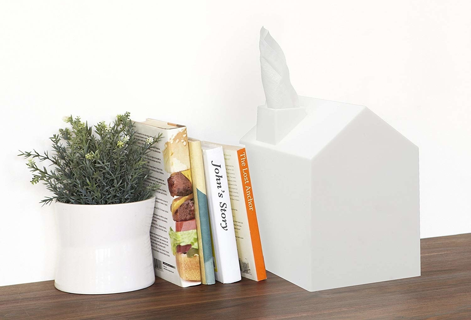 a white tissue box covered shaped like a house with a tissue coming out of the chimney like smoke