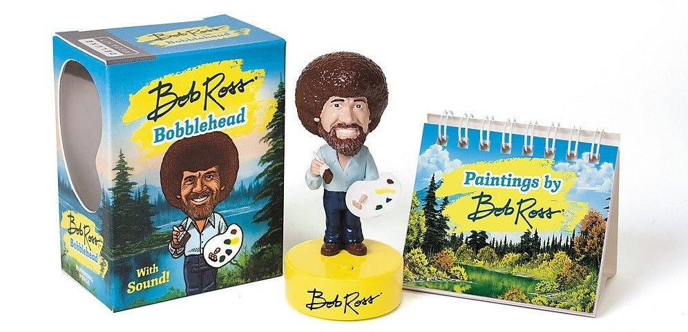The bobblehead with a mini book of Bob Ross paintings