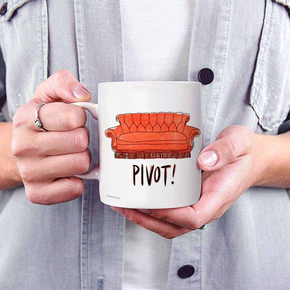 a white mug with a red couch on it and the word pivot!