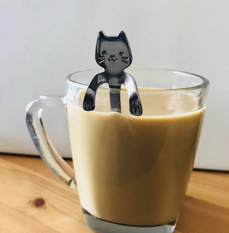 a small silver cat-shaped coffee spoon hanging over a mug