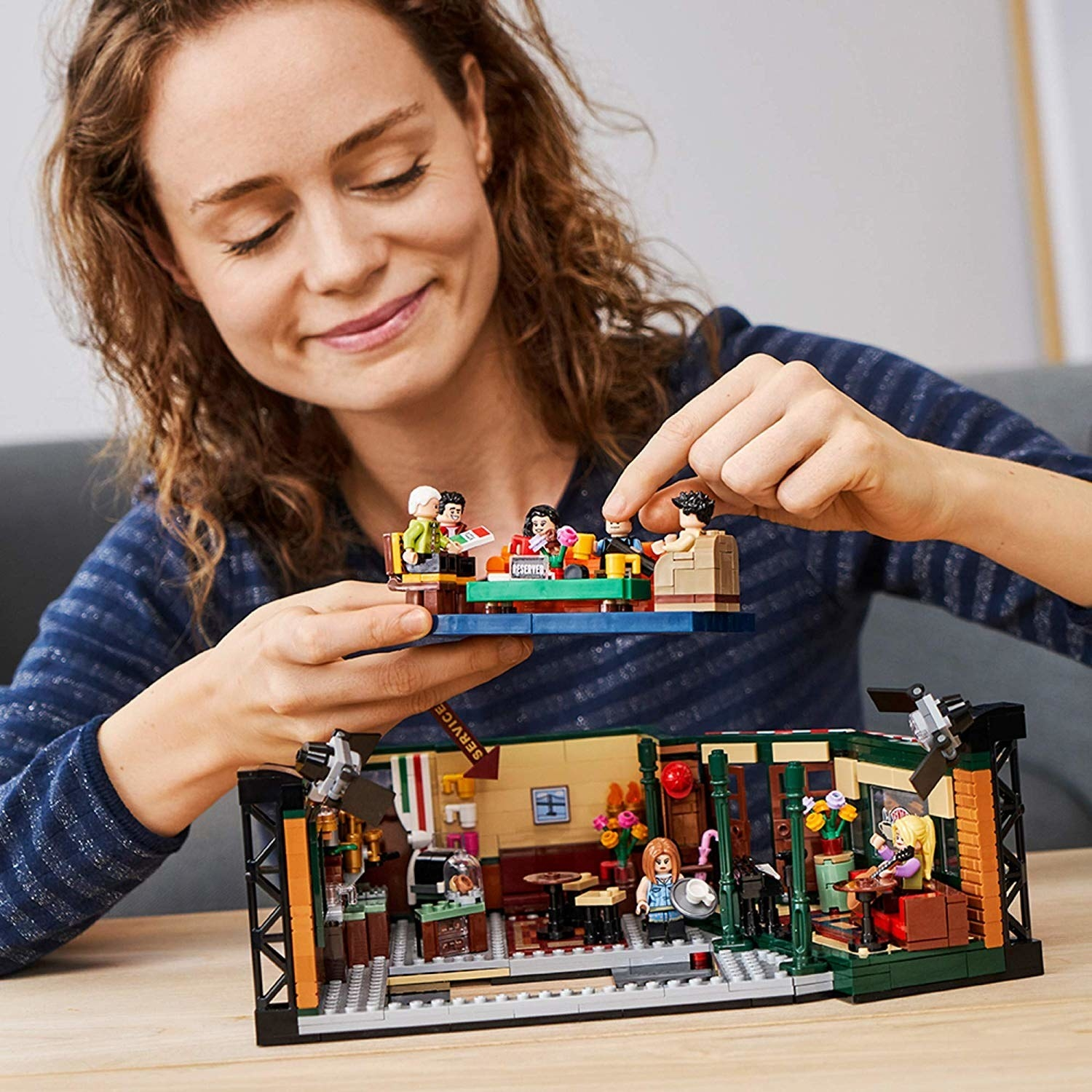 a model playing with a lego set that looks like the friends at central perk