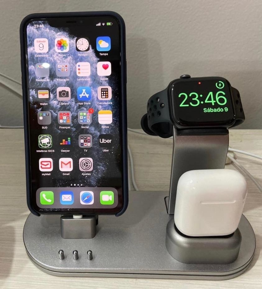 Reviewer photo of an iPhone, Apple Watch, and AirPods charging on the silver base