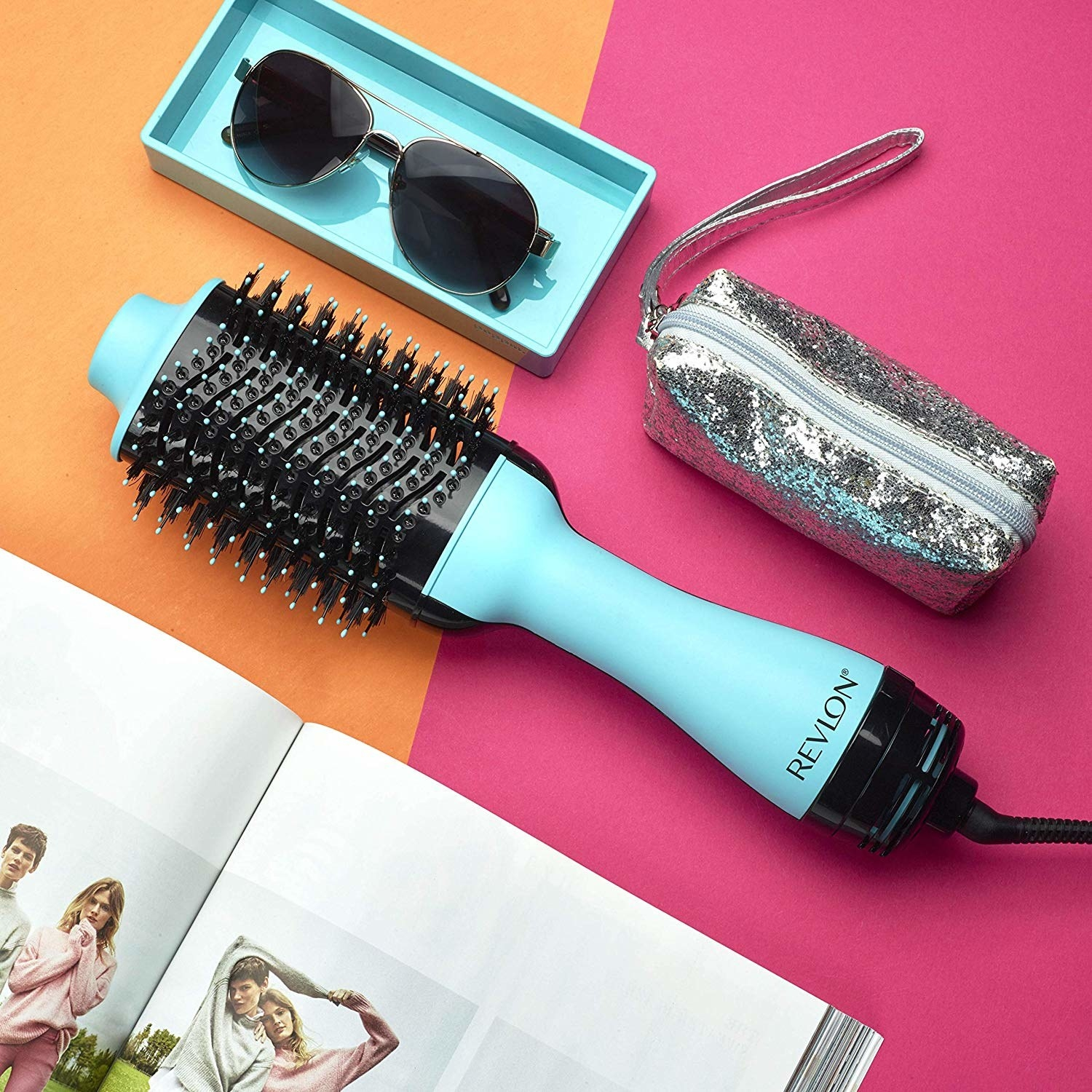 A large electronic hair brush with a pair of sunglasses and a cosmetic bag next to it