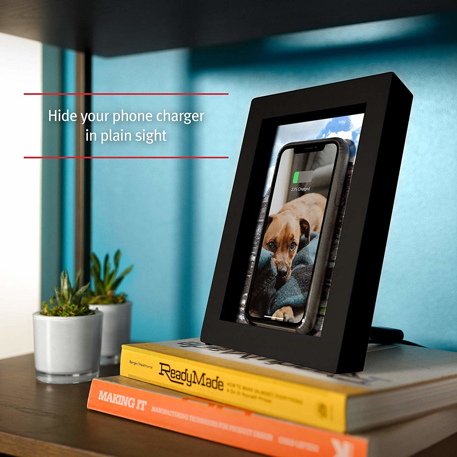The black frame with a phone propped up inside, getting charged