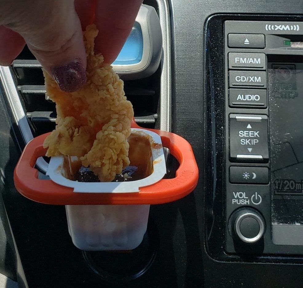 The clip attached to an air vent holding a sauce container