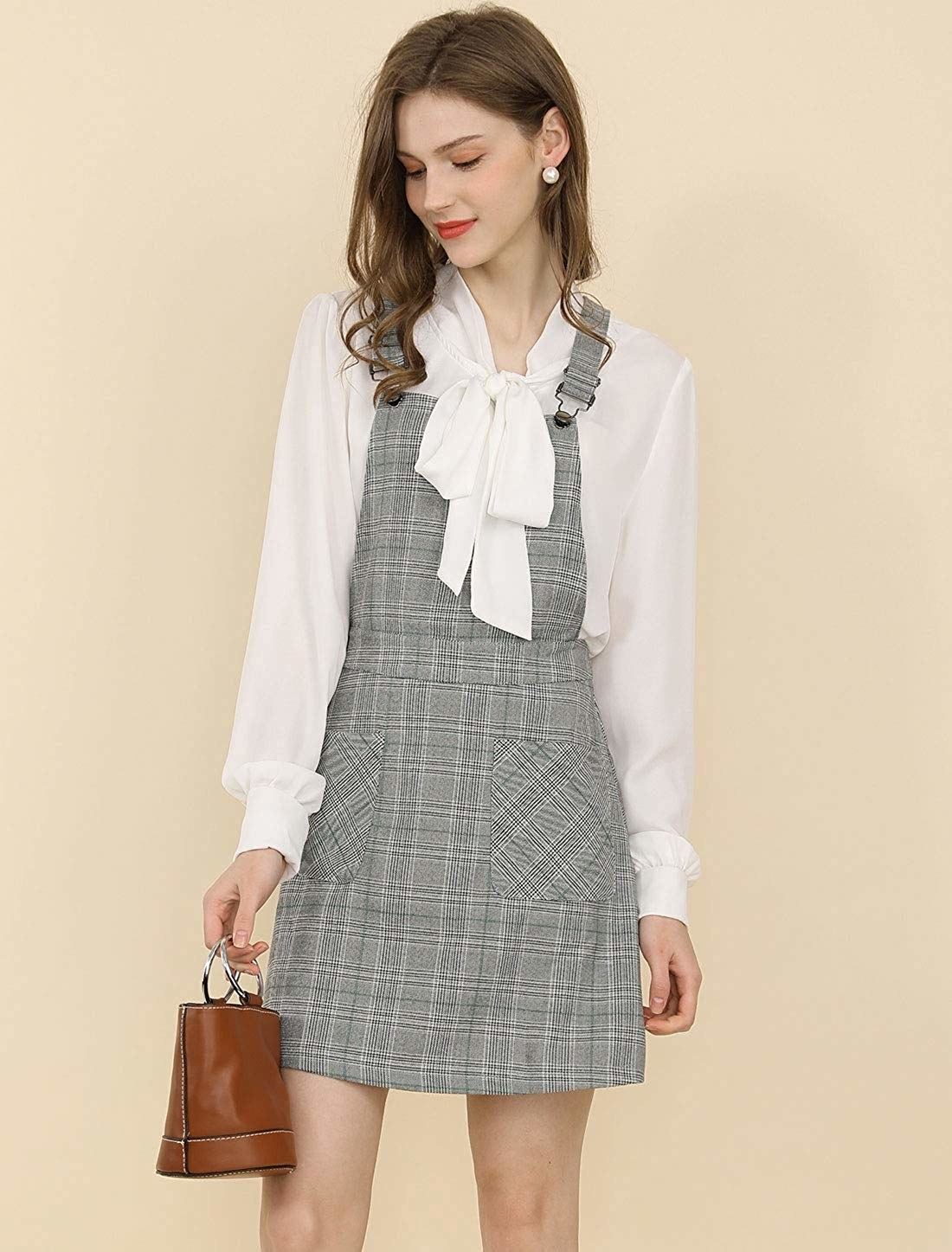 A model in the grey plaid dress with overall-style shoulder fasteners