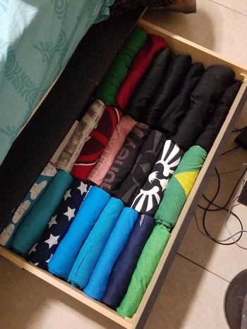 A reviewer's shirts folded neatly in a drawer, stacked sideways so they can see all the designs