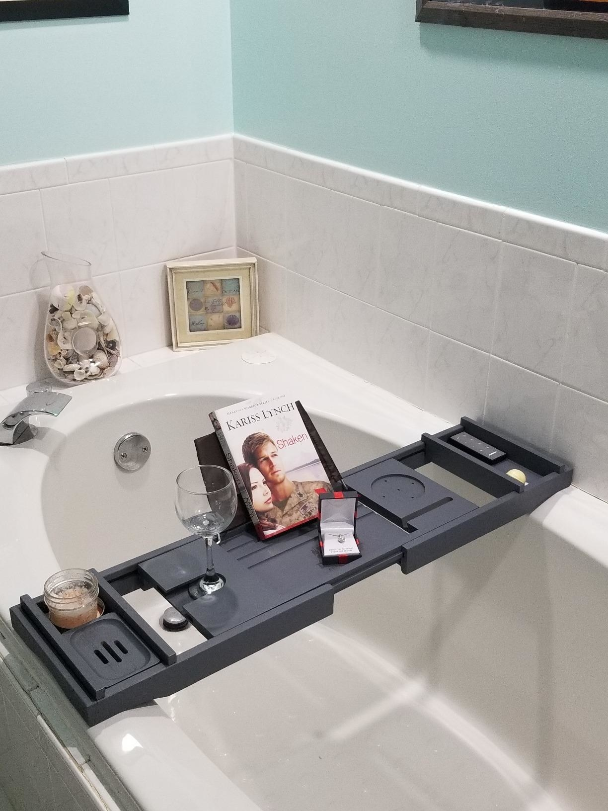 A reviewer showing the caddy on their tub
