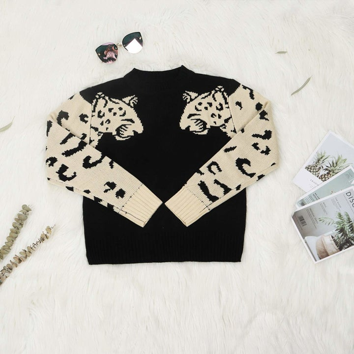 black sweater with white leopards on the sleeves