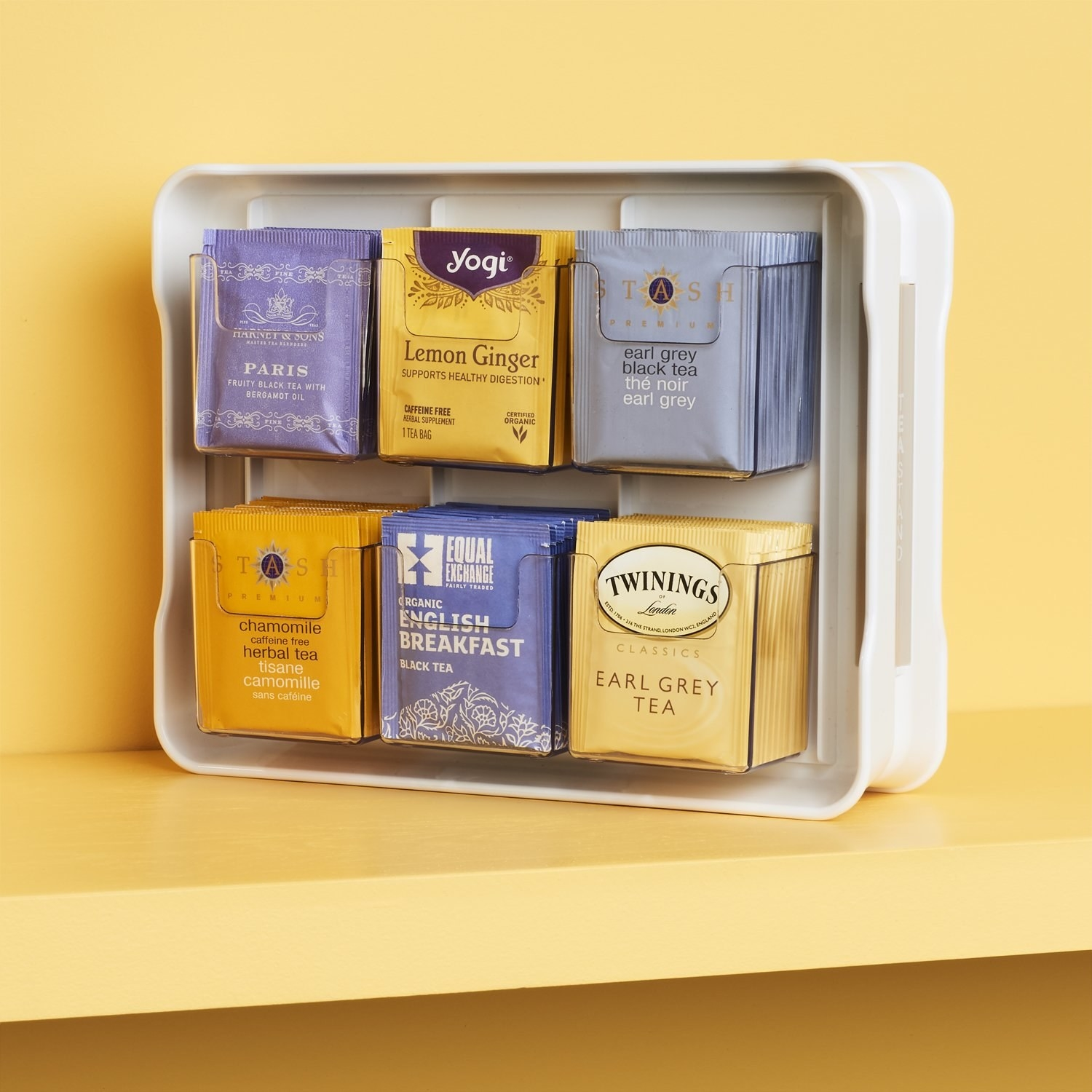 A plastic frame with six clear shelves that are fully stocked with tea packages