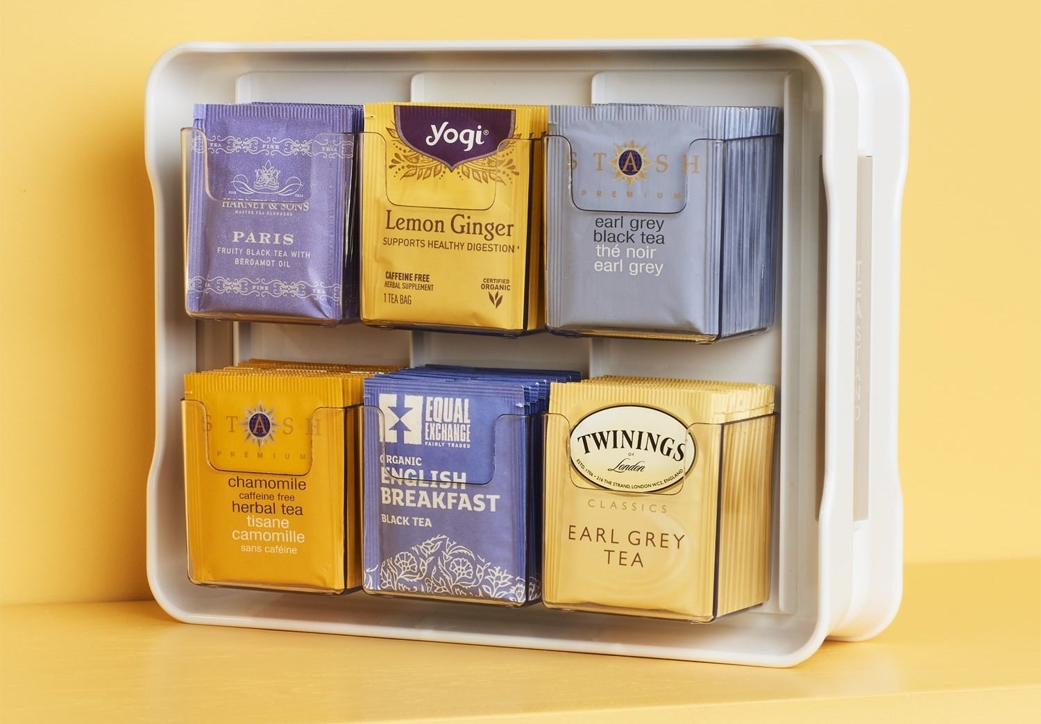 A large plastic panel with six pockets filled with different types of tea packages