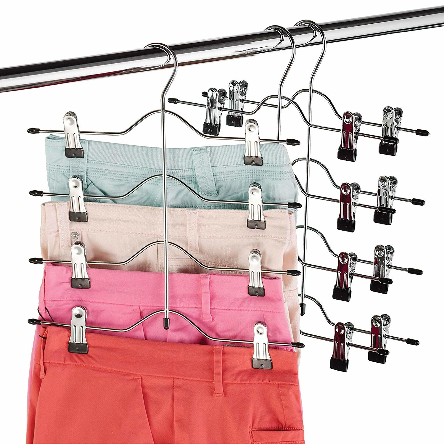 Four pairs of pants hanging from a hanger with clips on the ends