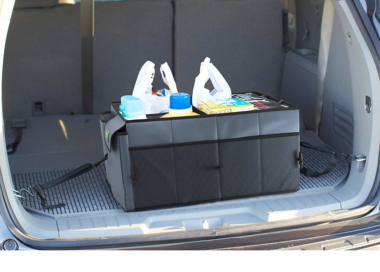 A large rectangular fabric box in the back of a car filled with groceries There are straps on each side that are connected to clips on the sides of the car