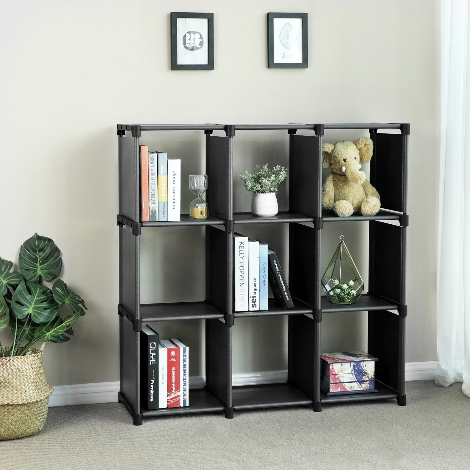 A shelving unit with nine square sections filled with books, plants, and stuffed animals