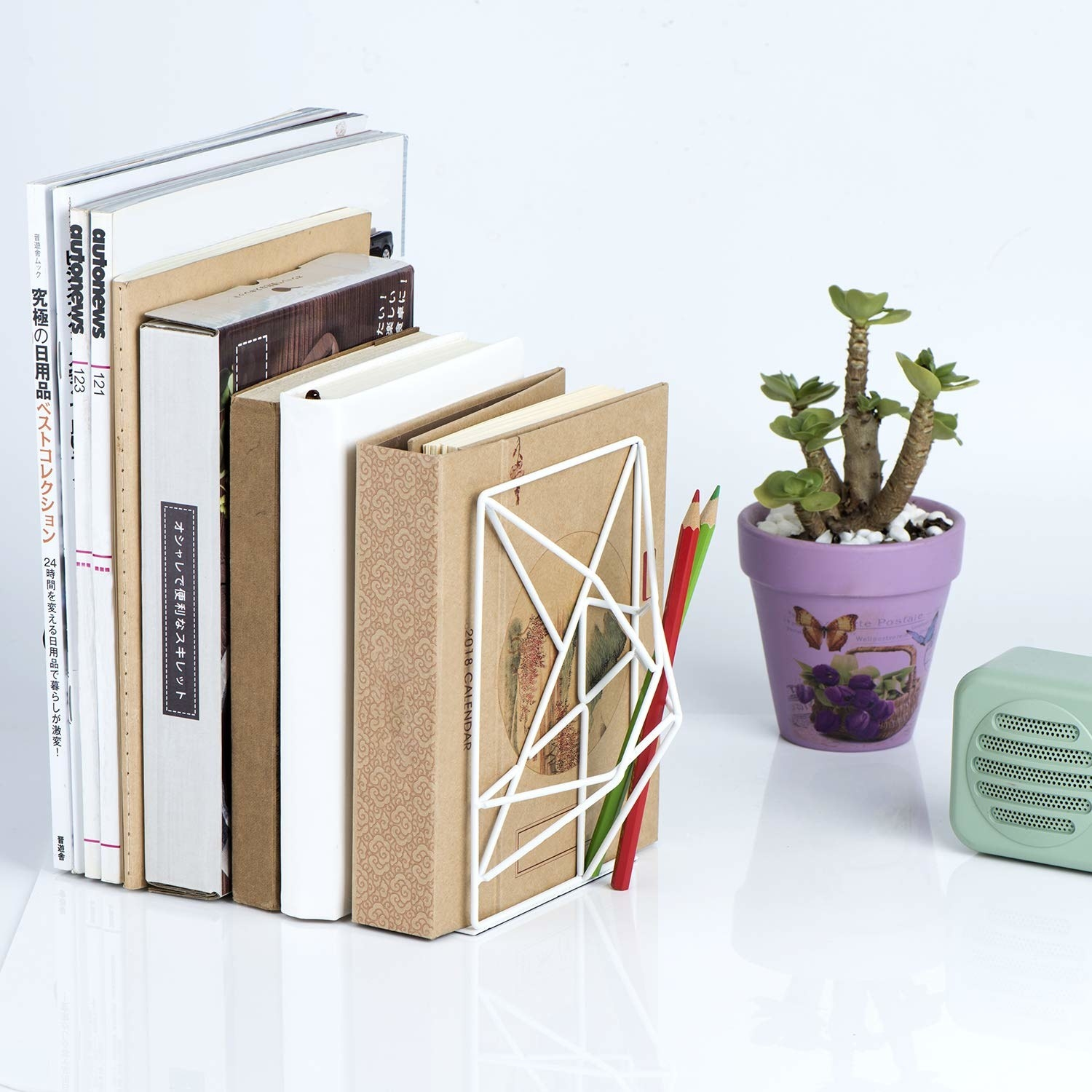 A stack of books with a wiry bookend on one side