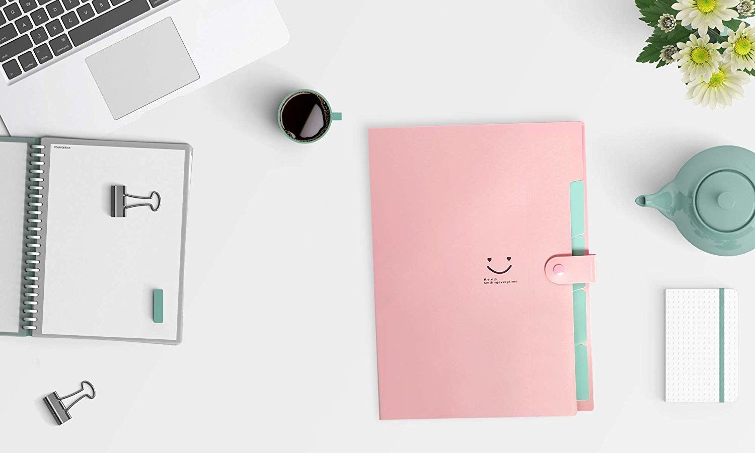 A plastic file folder with a smiley face on it lying on a desk near a laptop and notebook