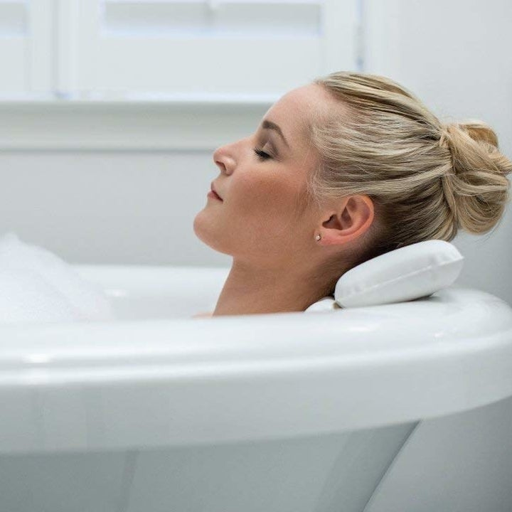 a model with their head resting on the pillow while in the bath