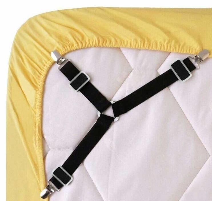 the bedsheet fasteners clipped on to the corners of a bedsheet on the under side of the mattress