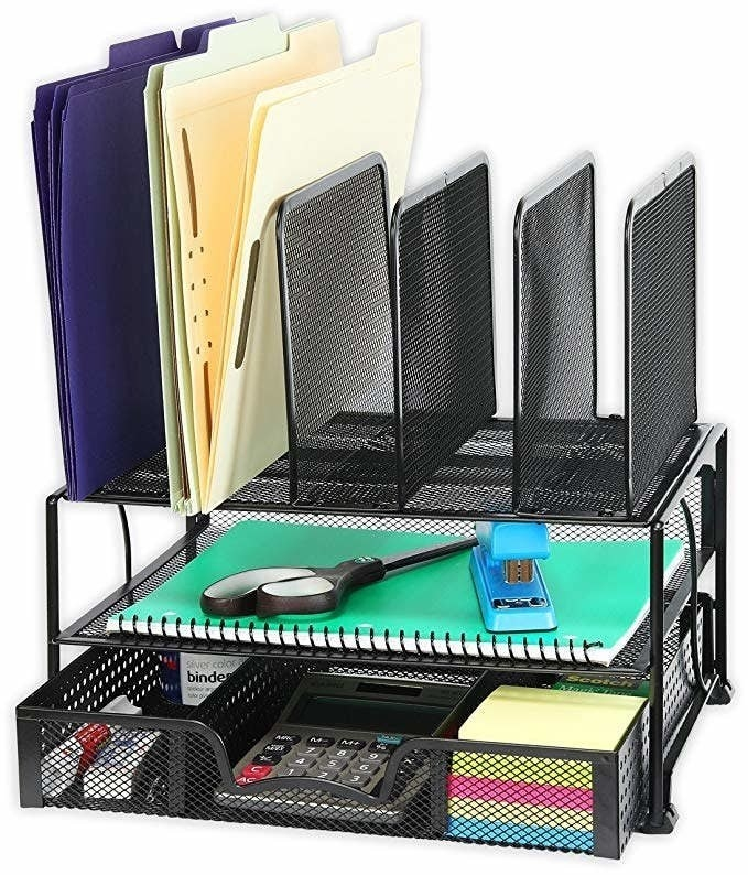 The mesh desk organizer in black holding sticky notes, folders, a calculator, scissors, a stapler, notebook, and more