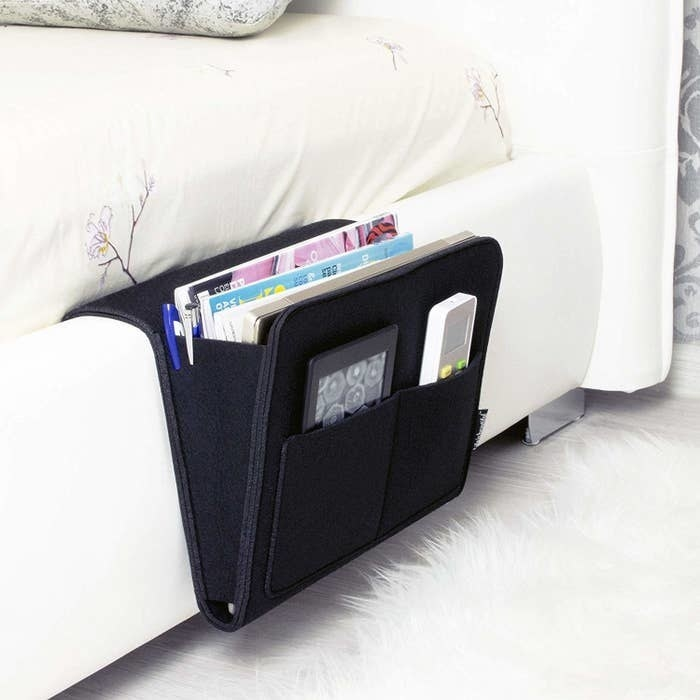 the bedside caddy in black hooked on the side of a bed