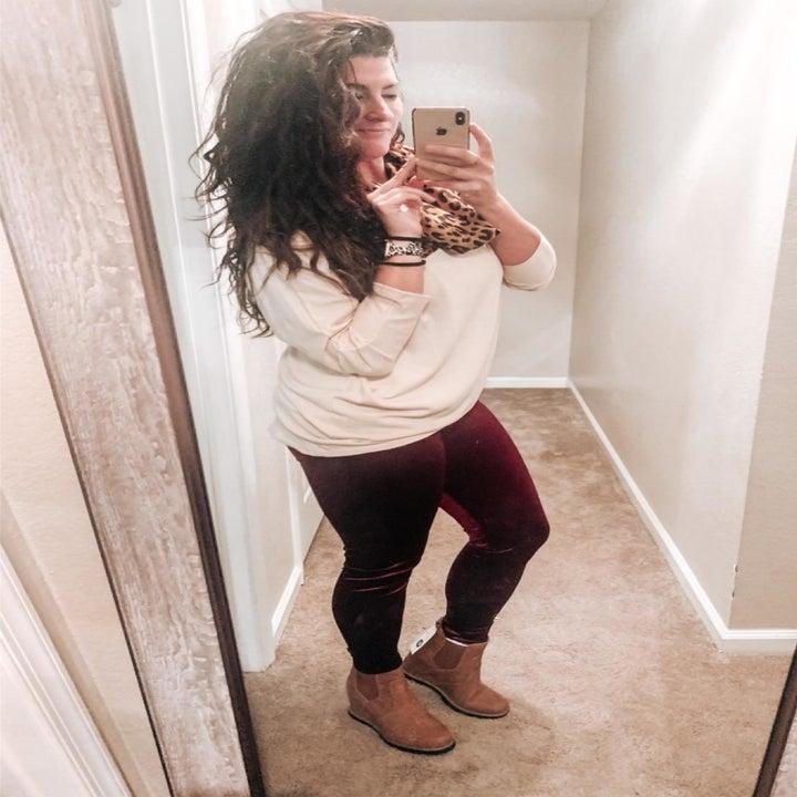 reviewer wearing off white top with burgundy velvet leggings