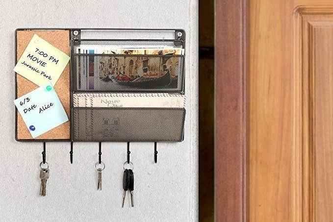 The black mesh mall sorter has a cork board, two mail slots, and five key hooks