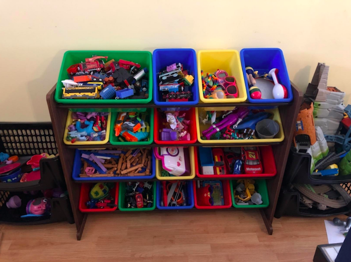 It has four shelves which are each filled with four bright containers filled with toys separated neatly in side
