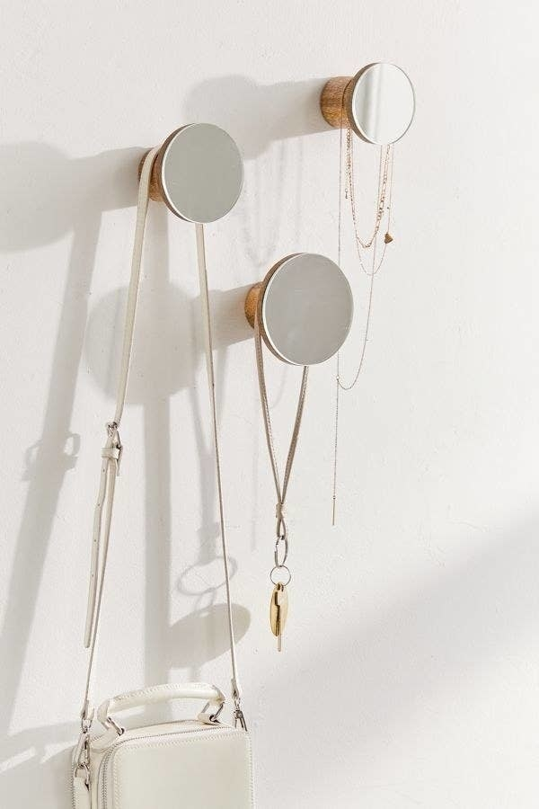 three wooden wall hooks with small round mirror on them holding necklaces, a small bag, and a lanyard