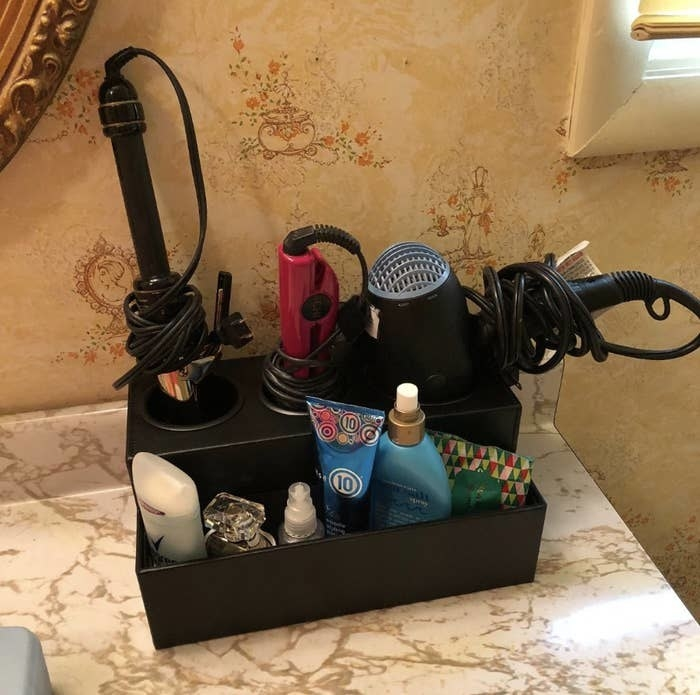 reviewer's countertop holder in black filled with hair tools and beauty products such as a blowdryer, straightening, curler, deodorant, and perfume